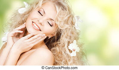 happy woman with flowers in hair - health and beauty concept...