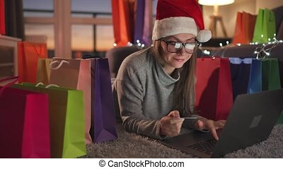 Happy woman with glasses wearing a santa claus hat is lying on the carpet and makes an online purchase using a credit card and laptop. Shopping bags around. Preparing for Christmas, online shopping, lifestyle technology