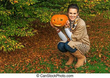 happy woman with Halloween pumpkin Jack O'Lantern