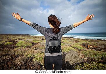 Happy woman with hands up enjoy ocean beach