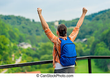 happy woman with hands up, enjoying freedom in nature