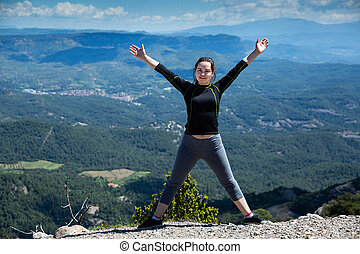 Happy woman with hands up on edge of mountain