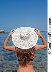 Happy woman with hat enjoying beach
