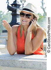 happy woman with hat talking on mobile phone
