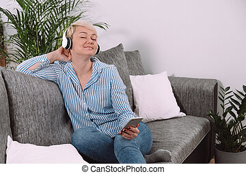 Happy woman with headphones and mobile phone listening to music and relaxing on sofa at home