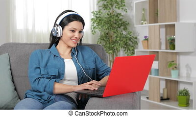 Happy woman wearing headphones browsing laptop content sitting on a couch at home