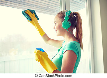 happy woman with headphones cleaning window - people, ...