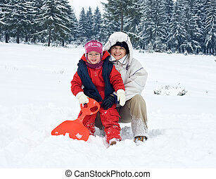 Happy woman with her daughter in winter time