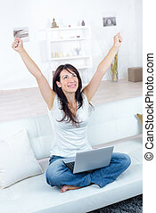 happy woman with laptop and credit card making online shopping