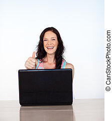 Happy woman with laptop and thumb up