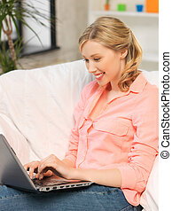 woman with laptop typing at home - happy woman with laptop...