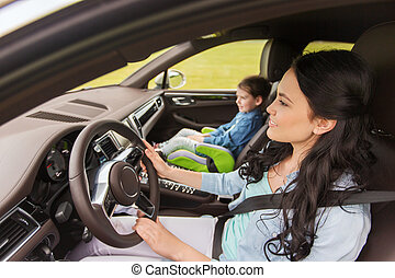 happy woman with little child driving in car