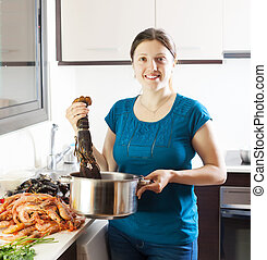 Happy woman with lobster in home