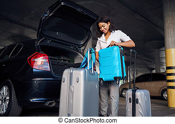 Happy woman with many suitcases in car parking