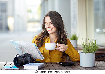 happy woman with map drinking cocoa at city cafe