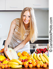 Happy woman with melon and other fruits