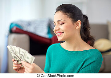 happy woman with money planning her travel at home