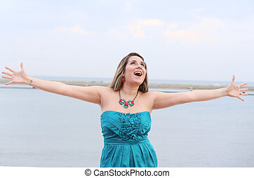 Happy woman with open arms looking at the sky