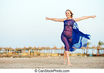 Happy woman with open arms on sea beach