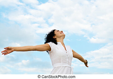 Happy smiling woman standing with outspread arms and her face lifted to the cloudy blue sky