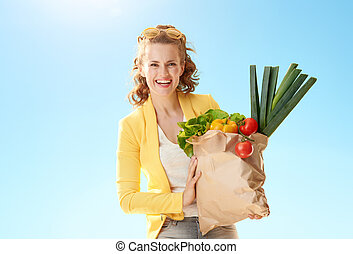 happy woman with paper bag with groceries against blue sky