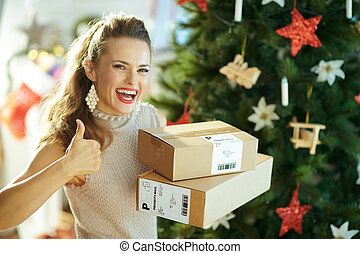 happy woman with parcels showing thumbs up near Christmas tree