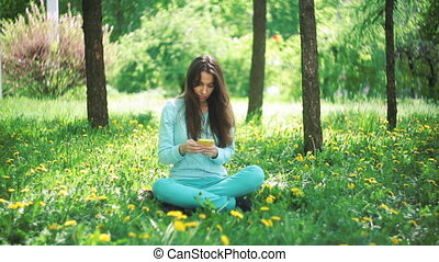 Happy woman with phone sitting on grass in blooming spring garden