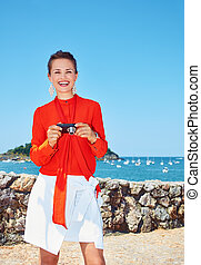 Happy woman with photo camera standing in front of lagoon