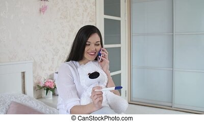 Happy woman with pregnancy test calling to husband - Woman...