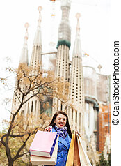 Happy woman with purchases in Barcelona