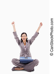 Happy woman with raised arms and laptop