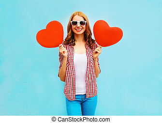 Happy woman with red air balloons in the shape of a heart on blue background