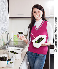 Happy woman with  seedlings at home kitchen