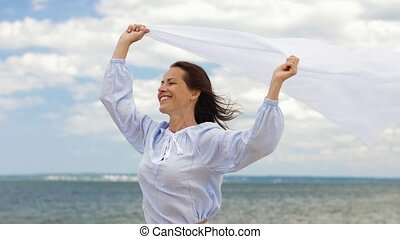 happy woman with shawl waving in wind on beach - people and...