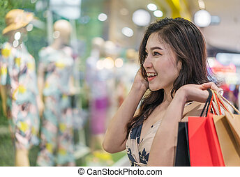 happy woman with shopping bags in clothes store