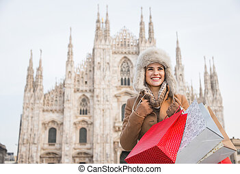 Happy woman with shopping bags in the front of Duomo, Milan