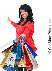 Happy woman with shopping bags pointing to copy