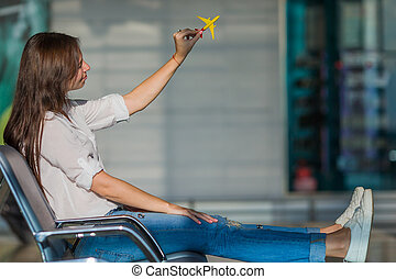 Happy woman with small model airplane and passports in airport