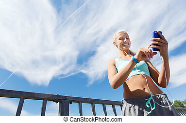 happy woman with smartphone and earphones outdoors - fitness...