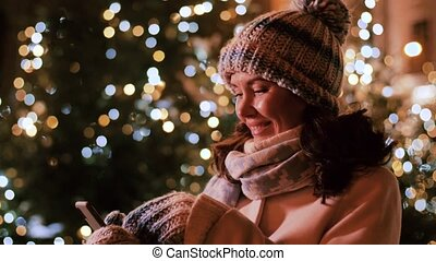 happy woman with smartphone in christmas city