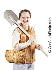 Happy woman with spade and basket - Happy mature woman with...