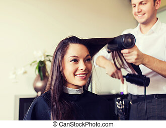 happy woman with stylist making hairdo at salon - beauty, ...