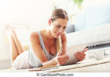 Happy woman with tablet at home