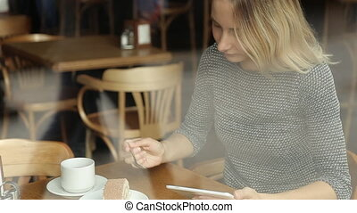 Happy woman with tablet computer in cafe