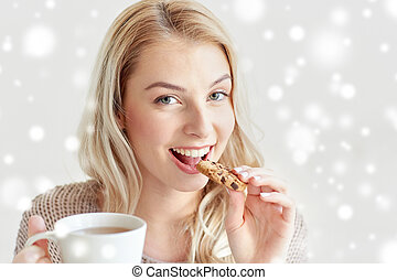 happy woman with tea eating cookie in winter