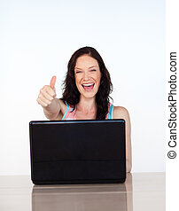 Happy woman with thumbs up using her laptop
