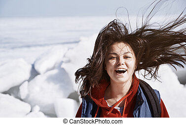 Happy woman with tousled hair having fun outdoors in icy landscape