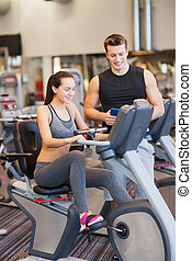 sport, fitness, lifestyle, technology and people concept - happy woman with trainer working out on exercise bike in gym