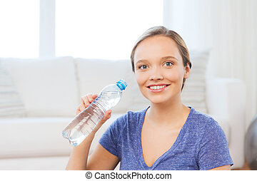 happy woman with water bottle at home