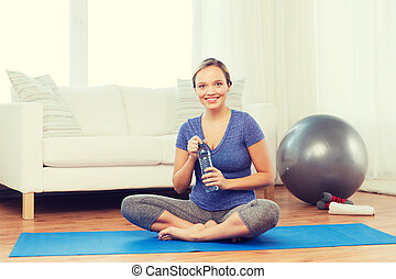 happy woman with water bottle exercising at home